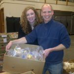 Springfield Rotarian's Liz Dahlager and Dan Hurley stop stuffing Snack Packs  to take a photo.